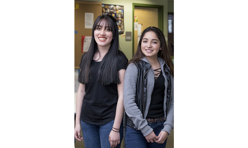 two female students standing and smiling